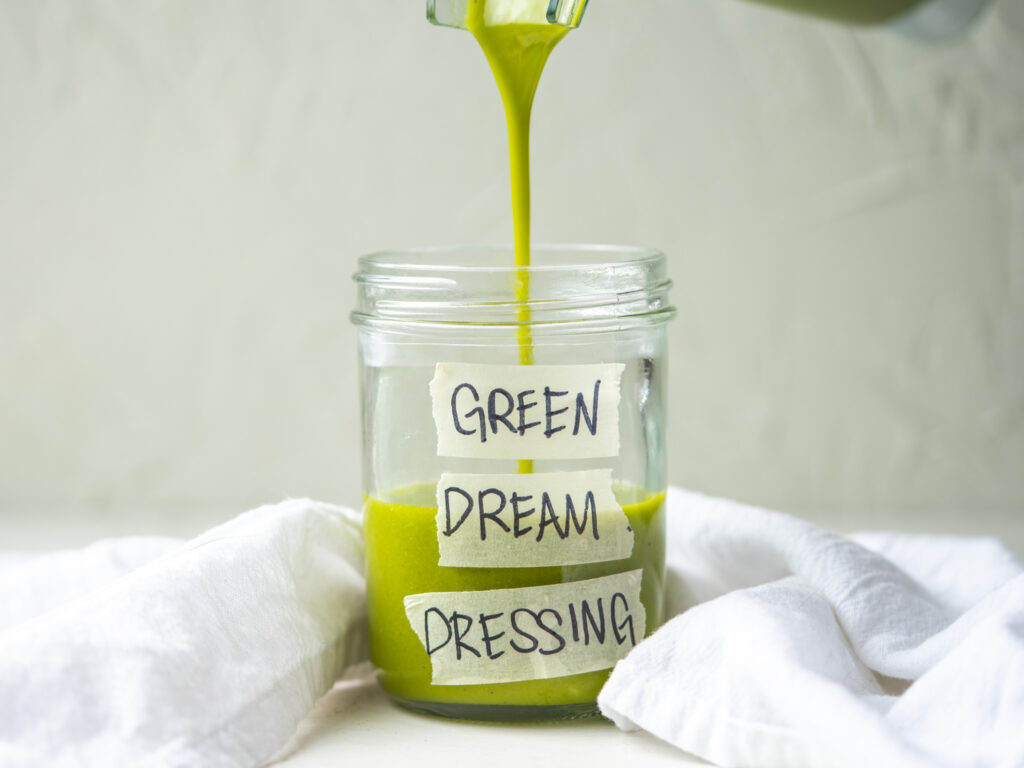Side view of green dream dressing pouring into a jar