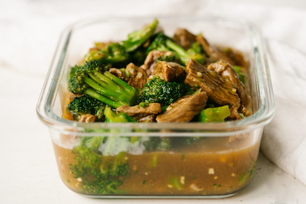 Side view of takeout style beef and broccoli in a glass storage container