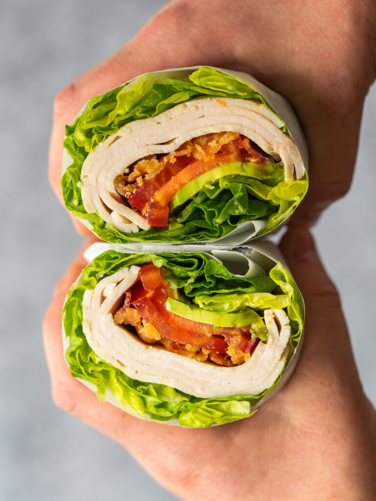 Side view of two hands holding a no bread turkey club cut in half
