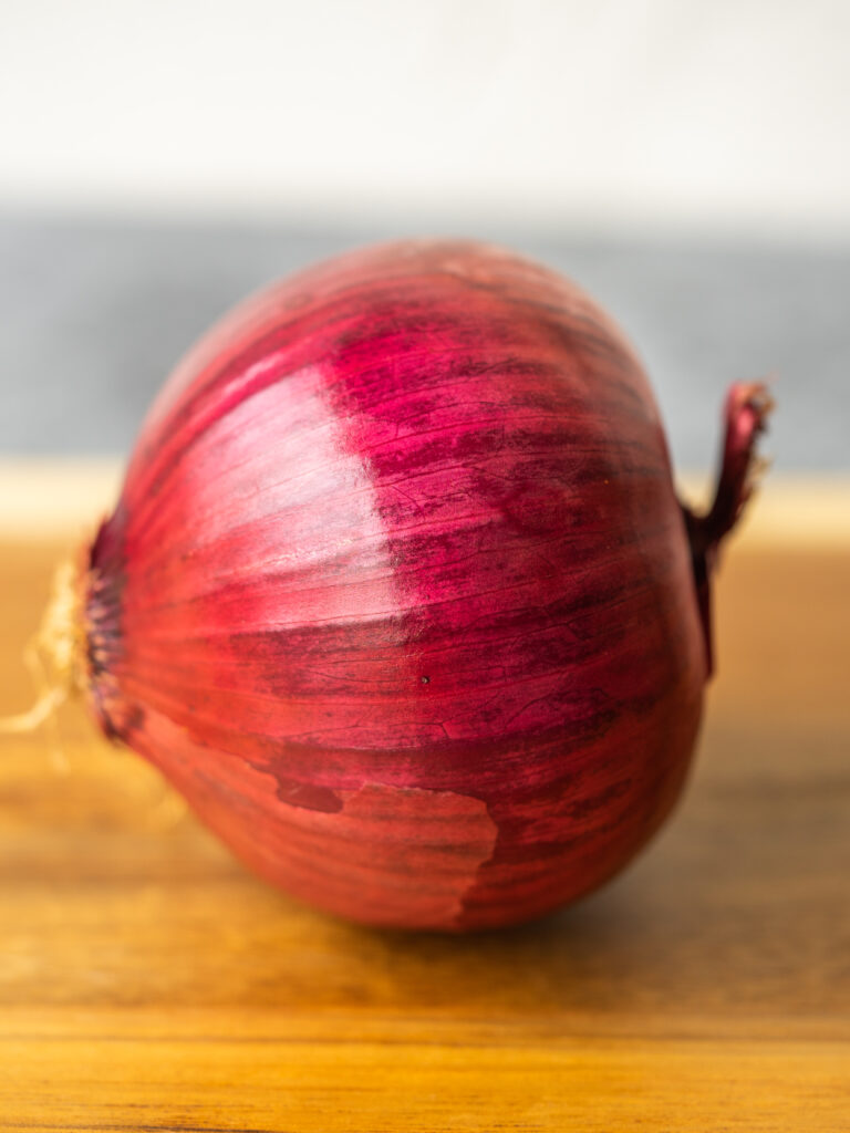 Side view of a red onion on a cutting board