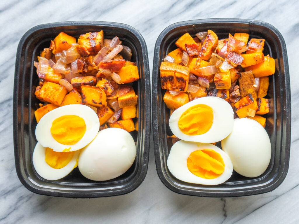 Above view of two premade paleo breakfasts with eggs, sweet potatoes in bacon in meal prep containers