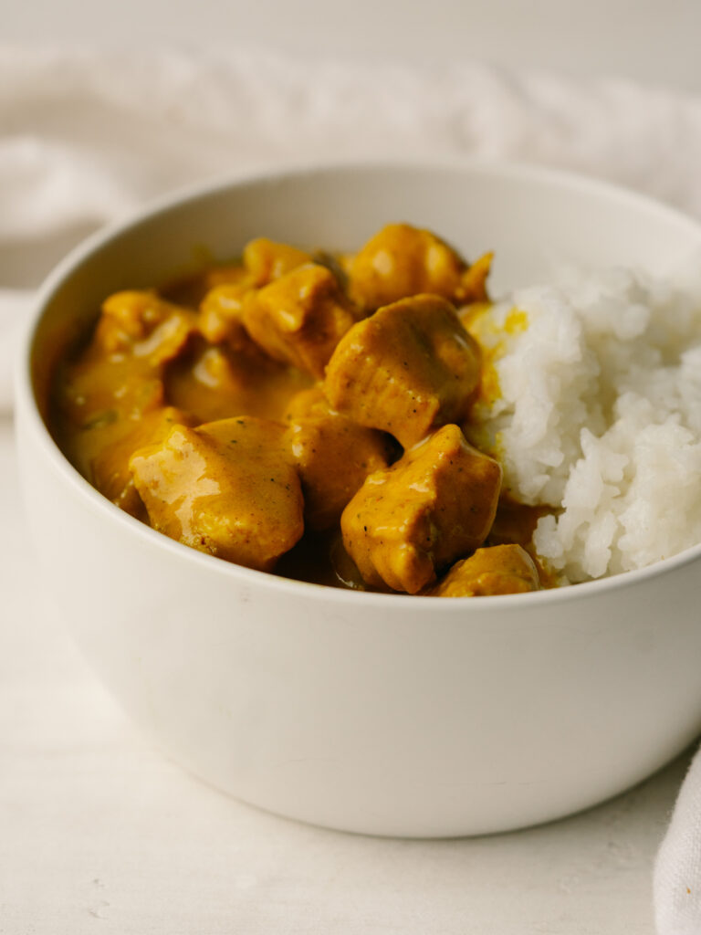 Three quarter view of pumpkin chicken curry in a bowl with rice