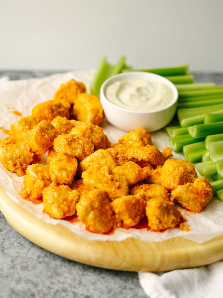 Three quarter view of buffalo chicken breast on a serving platter with ranch and celery