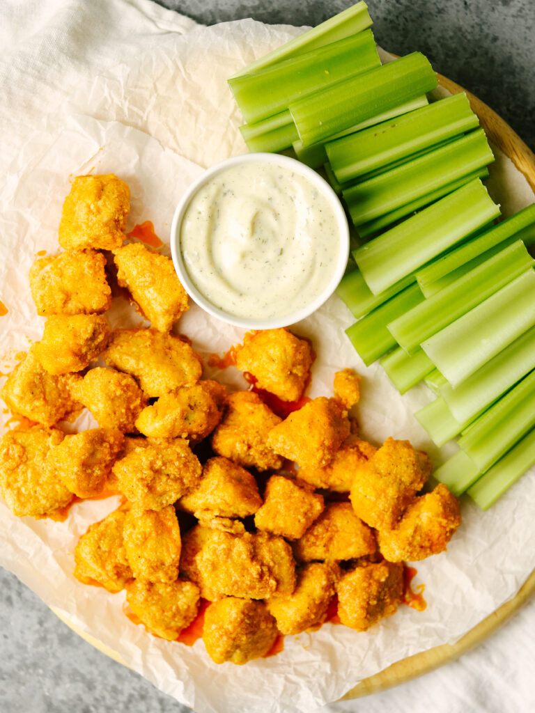 Above view of buffalo chicken breast on a serving platter with ranch and celery sticks