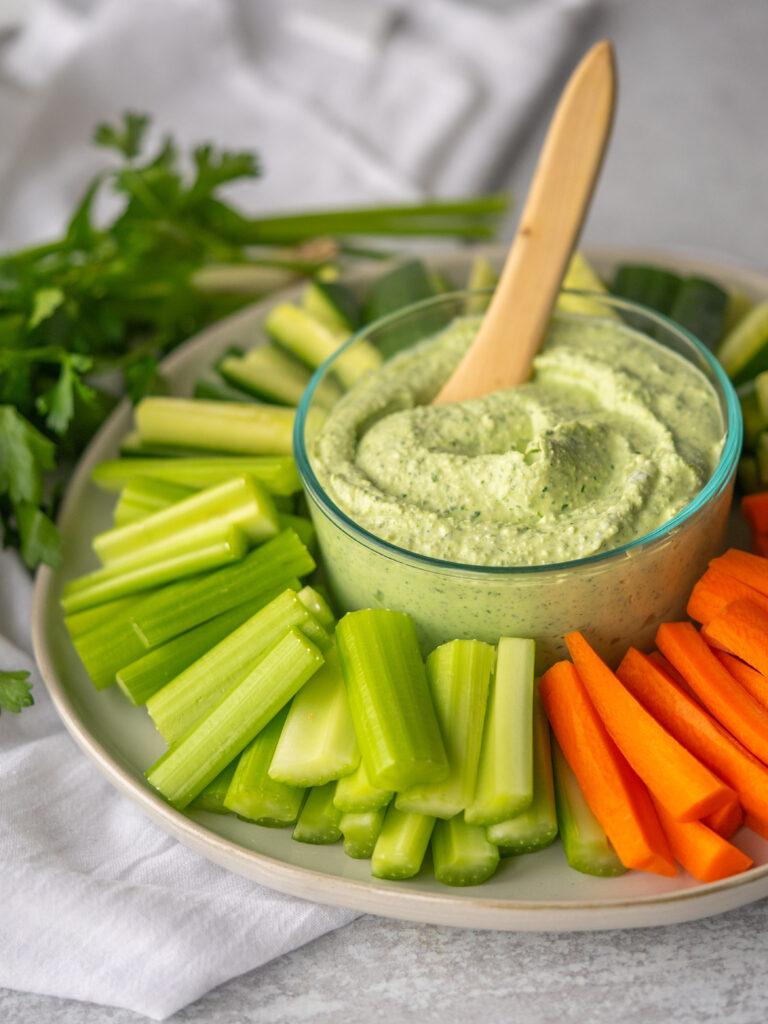 Three quarter view of whipped feta recipe with fresh herbs and raw veggies
