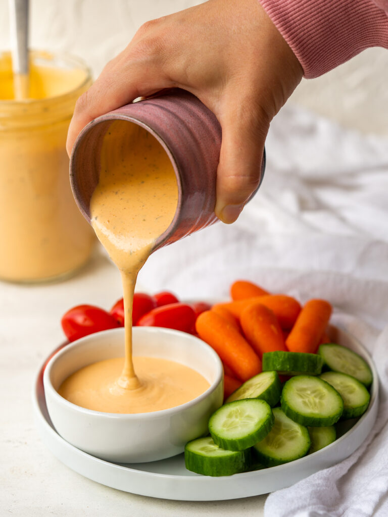 small jar of spicy ranch dressing pouring into a ramekin