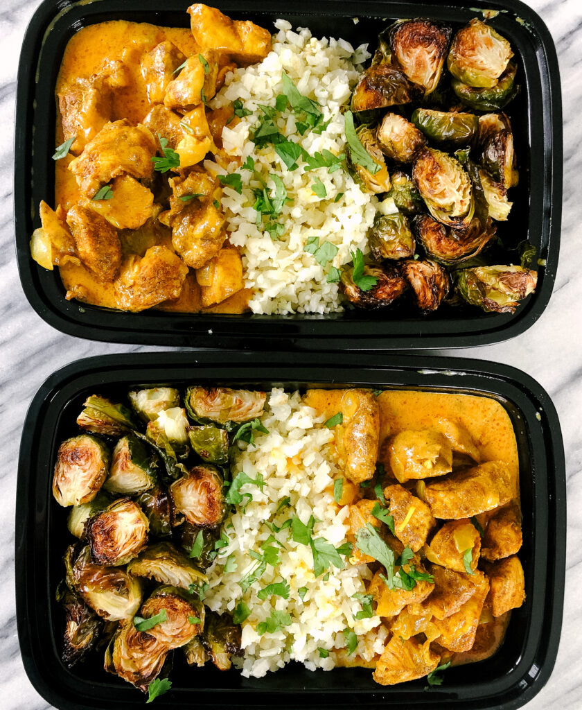 Above view of healthy butter chicken with cauliflower rice and roasted brussels sprouts in meal prep containers