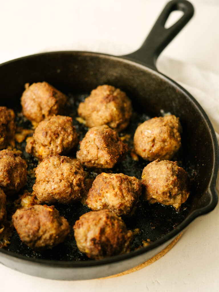 Close up three quarter view of beef meatballs in a cast iron skillet