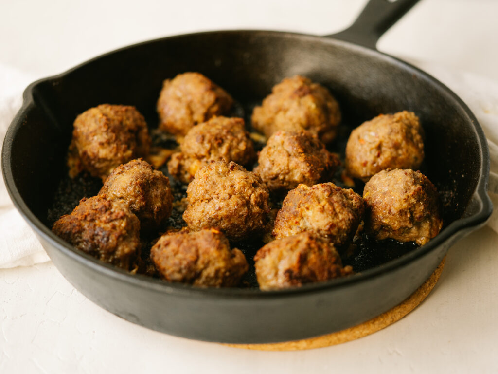 Three quarter view of cast iron meatballs in a cast iron skillet
