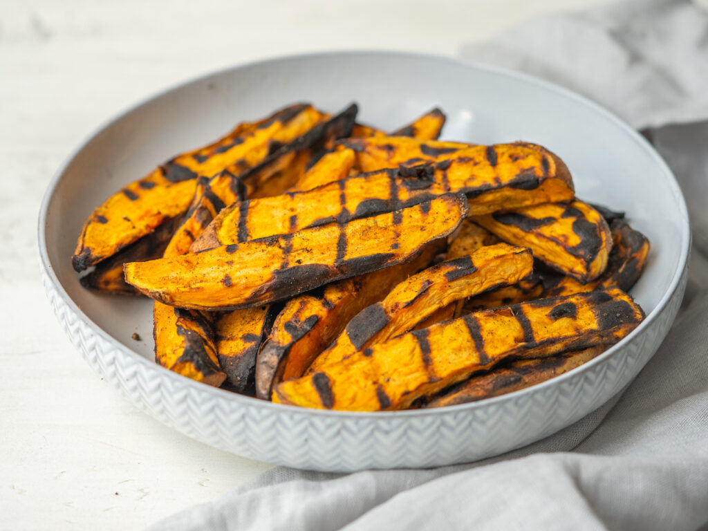 Three quarter view of grilled sweet potato wedges in a white serving bowl