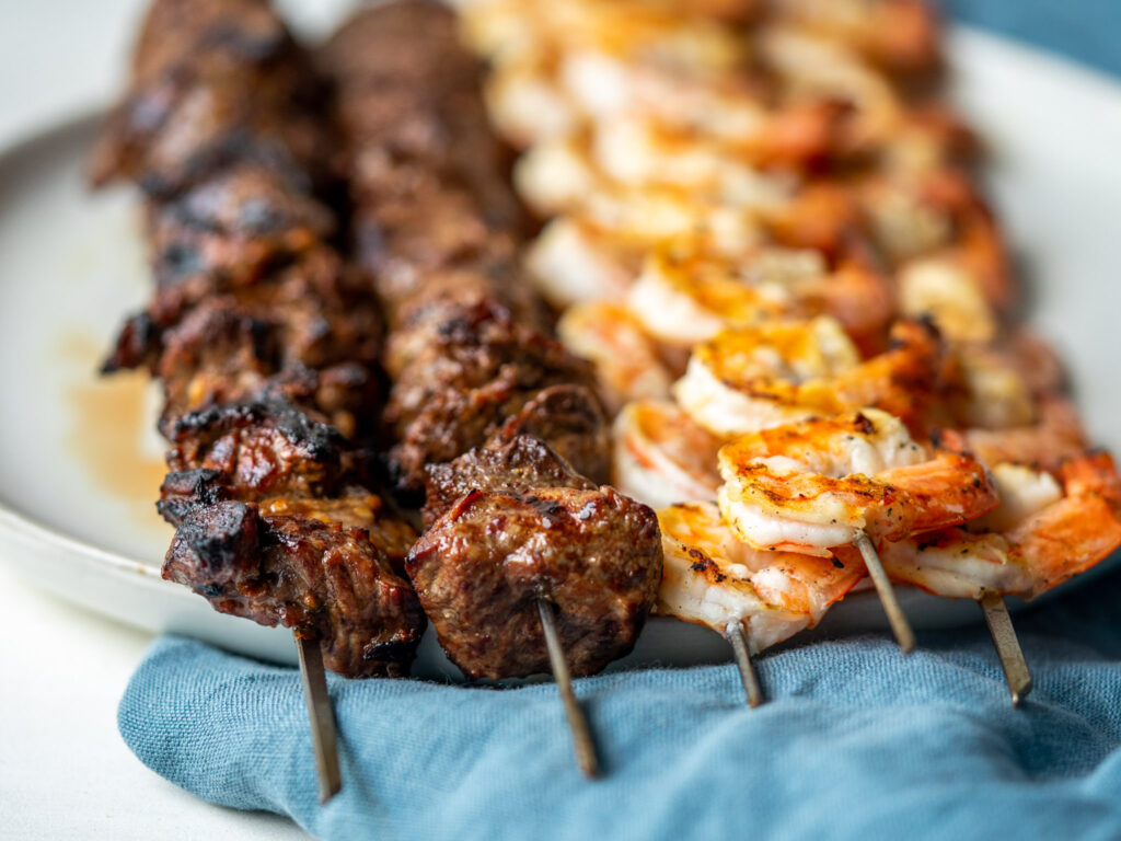 Side view of steak and shrimp kabobs on a serving plate