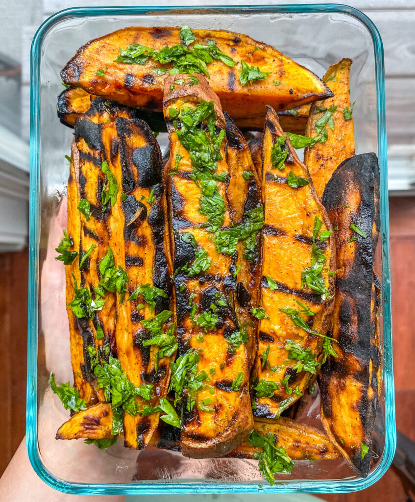 Leftover grilled sweet potato wedges in a glass storage container