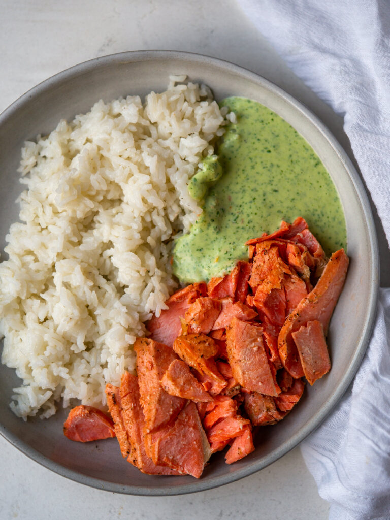 above view of lemon salmon, white rice, and a creamy herb sauce on a plate