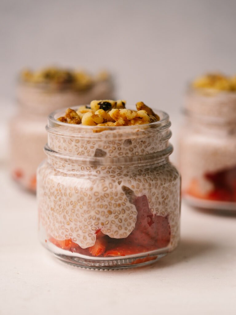Side view of a jar of homemade chia seed pudding with walnuts on top