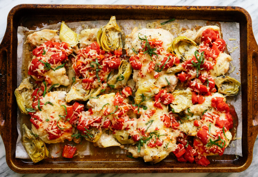Above view of a chicken artichoke bake with tomatoes on a sheet pan