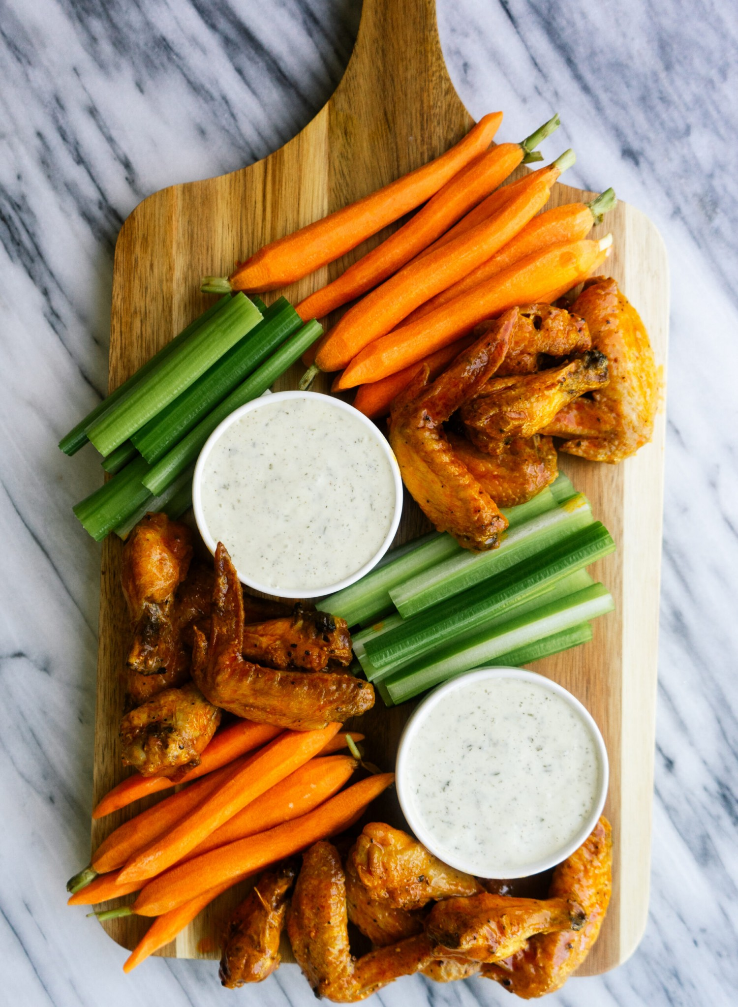 Above view of air fryer buffalo wings on a serving platter with homemade ranch dressing and raw veggies