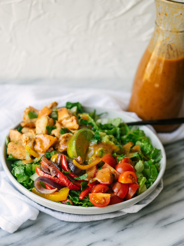 Vertical view of a homemade chipotle salad with the honey chipotle vinaigrette in the background