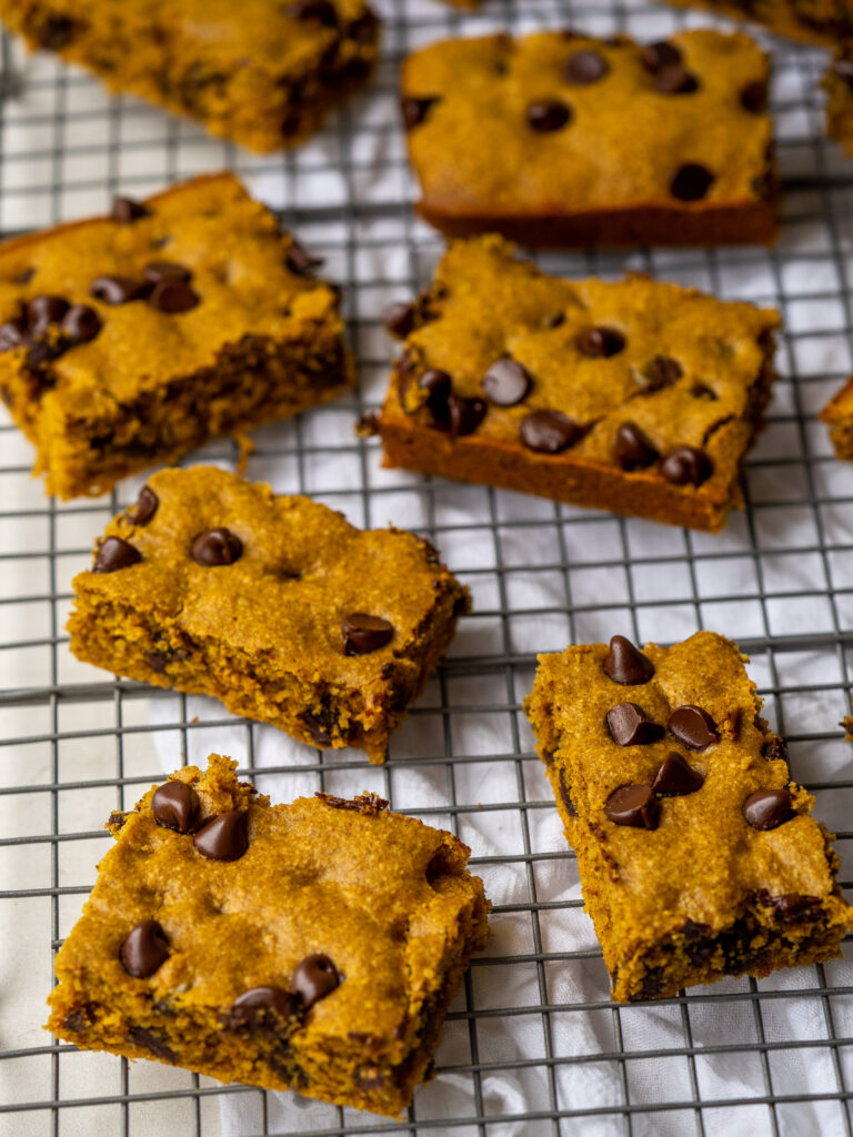 Three quarter view of pumpkin cookie bars on a cooling rack