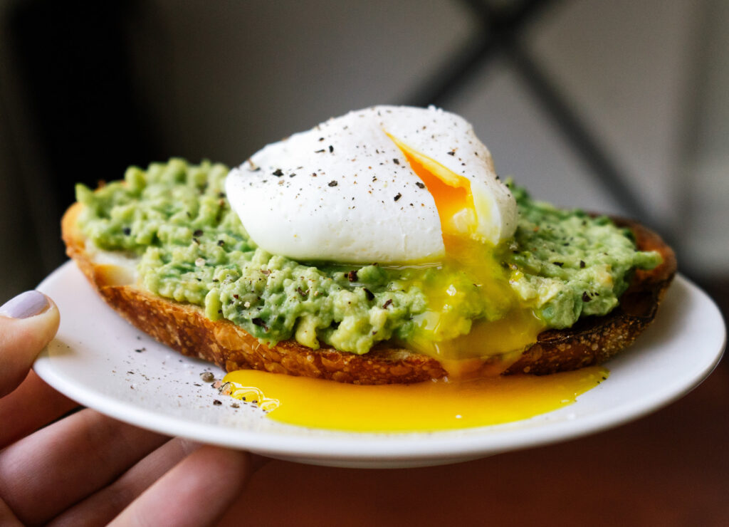 side view of  a poached egg on a piece of avocado toast. The poached egg is sliced open and yolk is coming out.