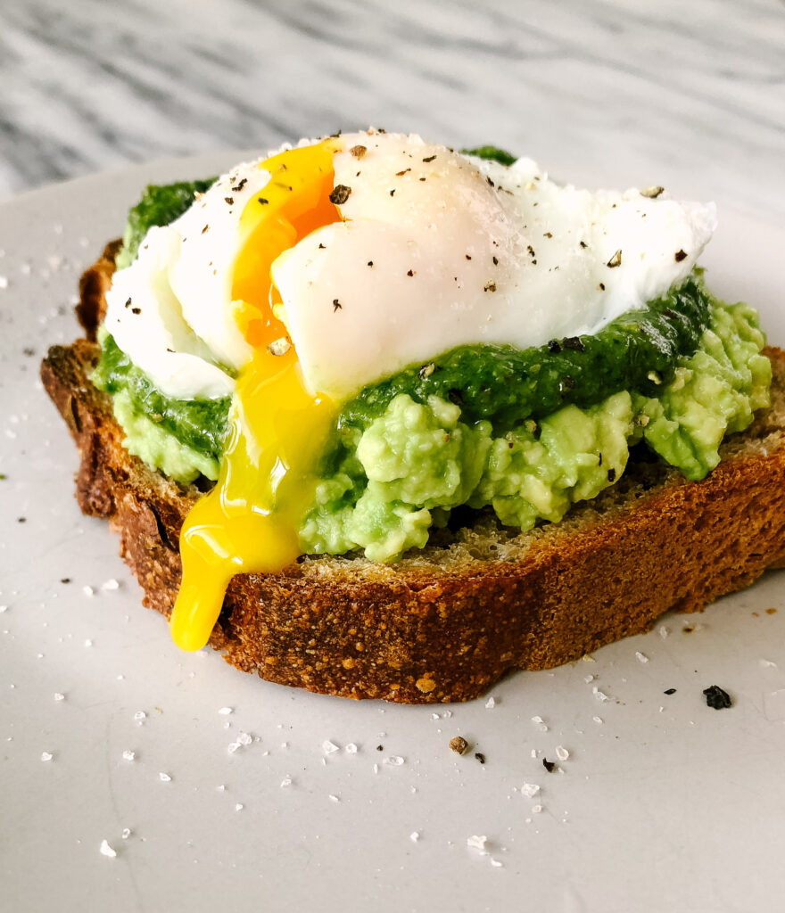three quarter view of  a perfect poached egg on a piece of avocado toast with pesto. The poached egg is sliced open and yolk is coming out.