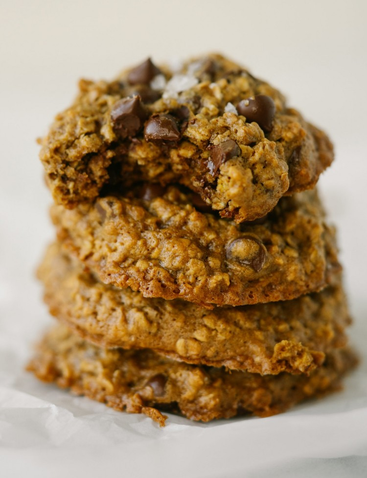 Side view of peanut butter oatmeal chocolate chip cookies stacked up with a bite out of the top cookie