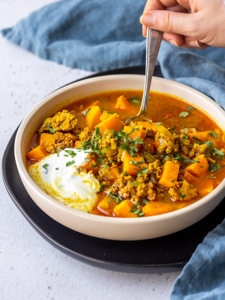 hand grabbing a spoonful of sweet potato and sausage curry soup