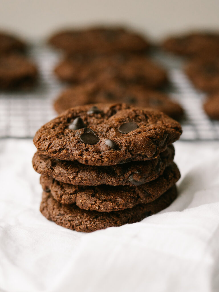 stack of chocolate chip mocha cookies with more cookies in background