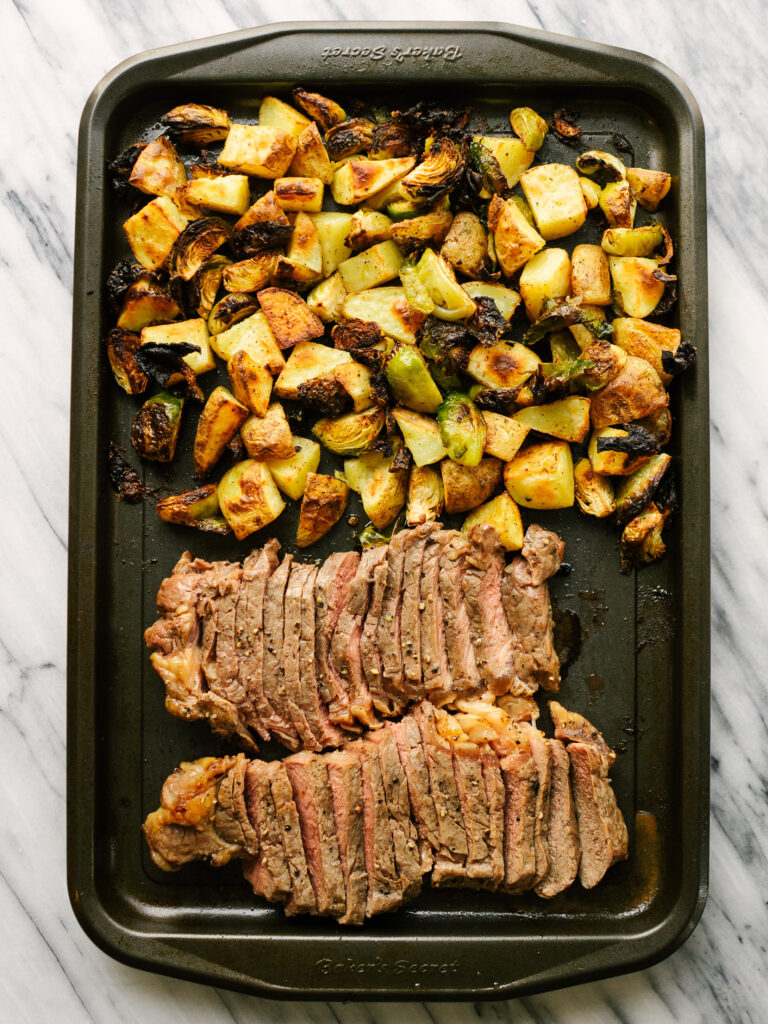 above view of steak and veggies on a sheet pan