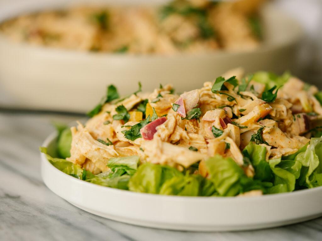Side view of fajita chicken salad on lettuce on a plate