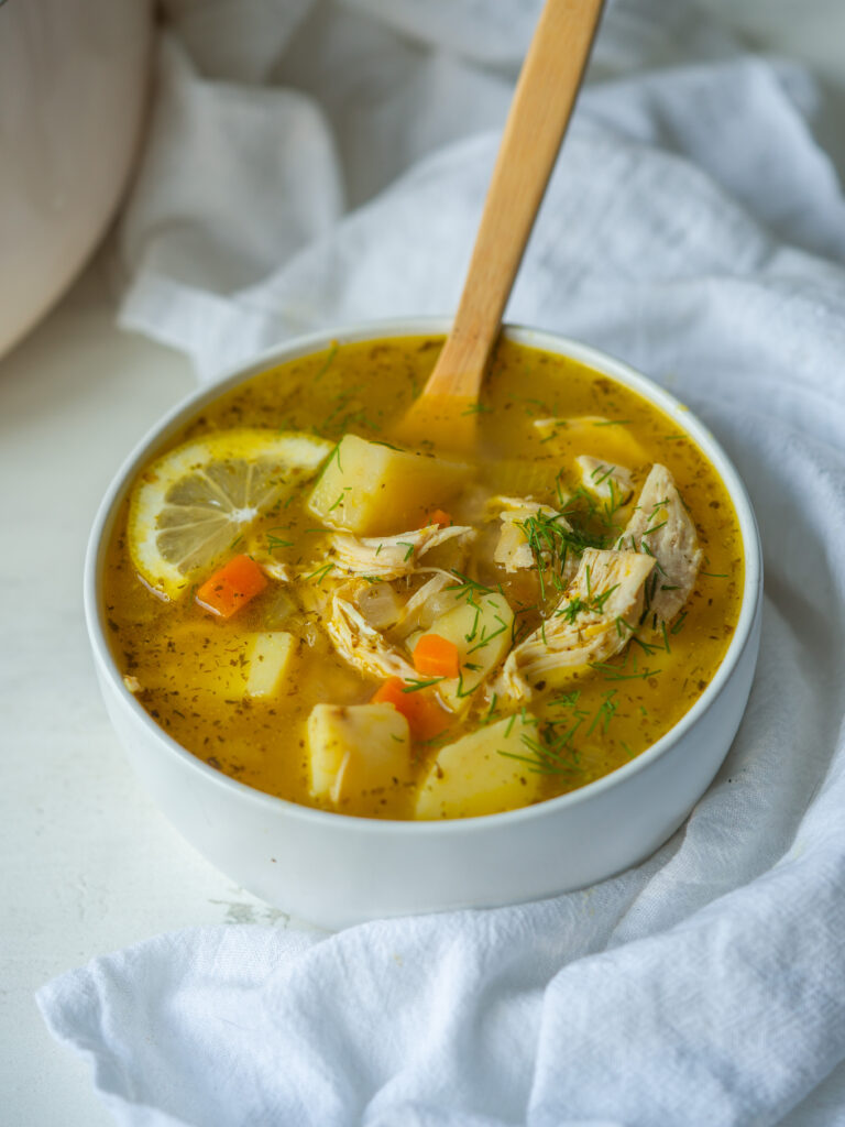 Three quarter view of Greek Lemon Chicken Soup in a serving bowl with a spoon