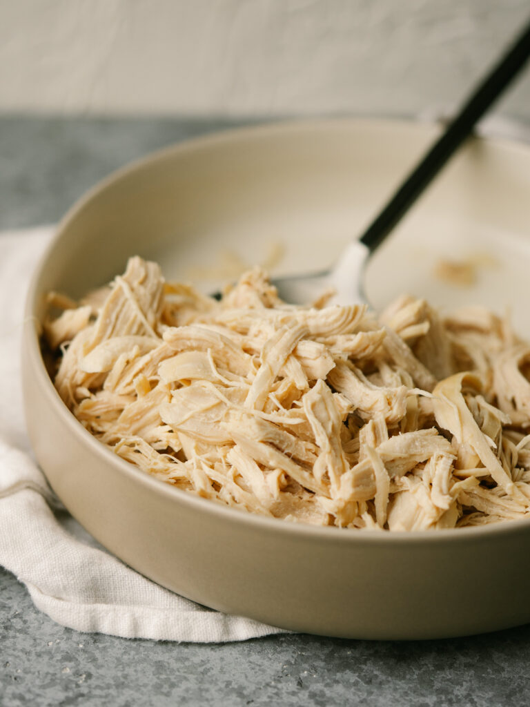 three quarter view of a bowl of shredded chicken with a spoon in it