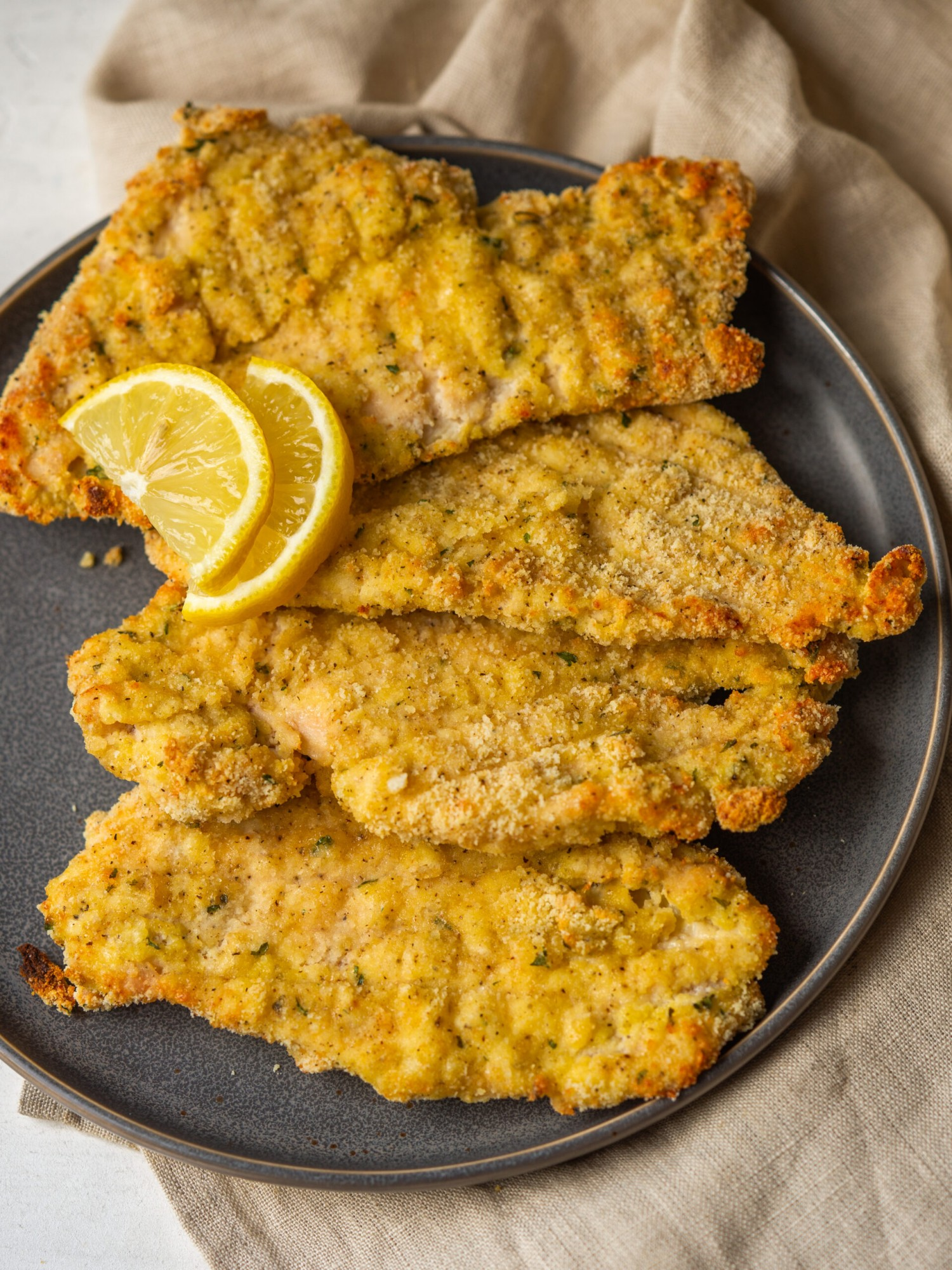 Above view of baked chicken cutlets on a plate with lemon slices