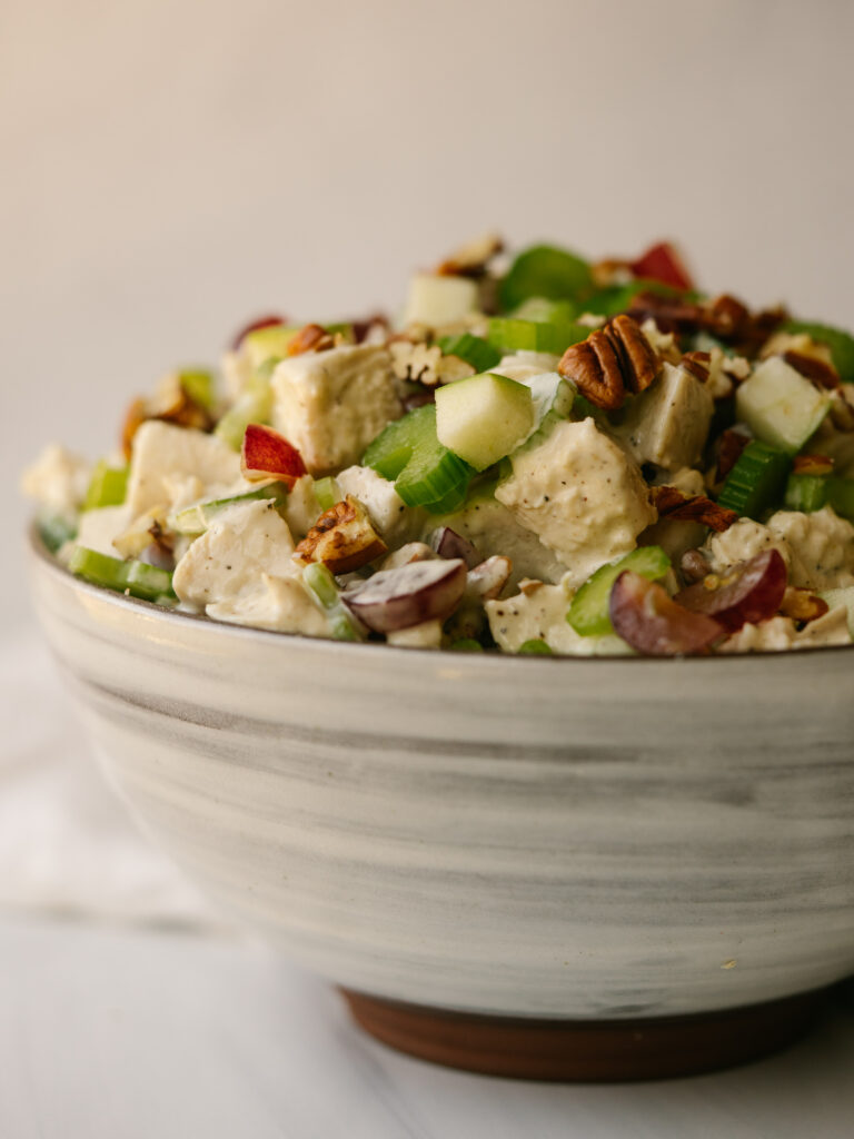 Close up side view of a healthy waldorf chicken salad in a mixing bowl