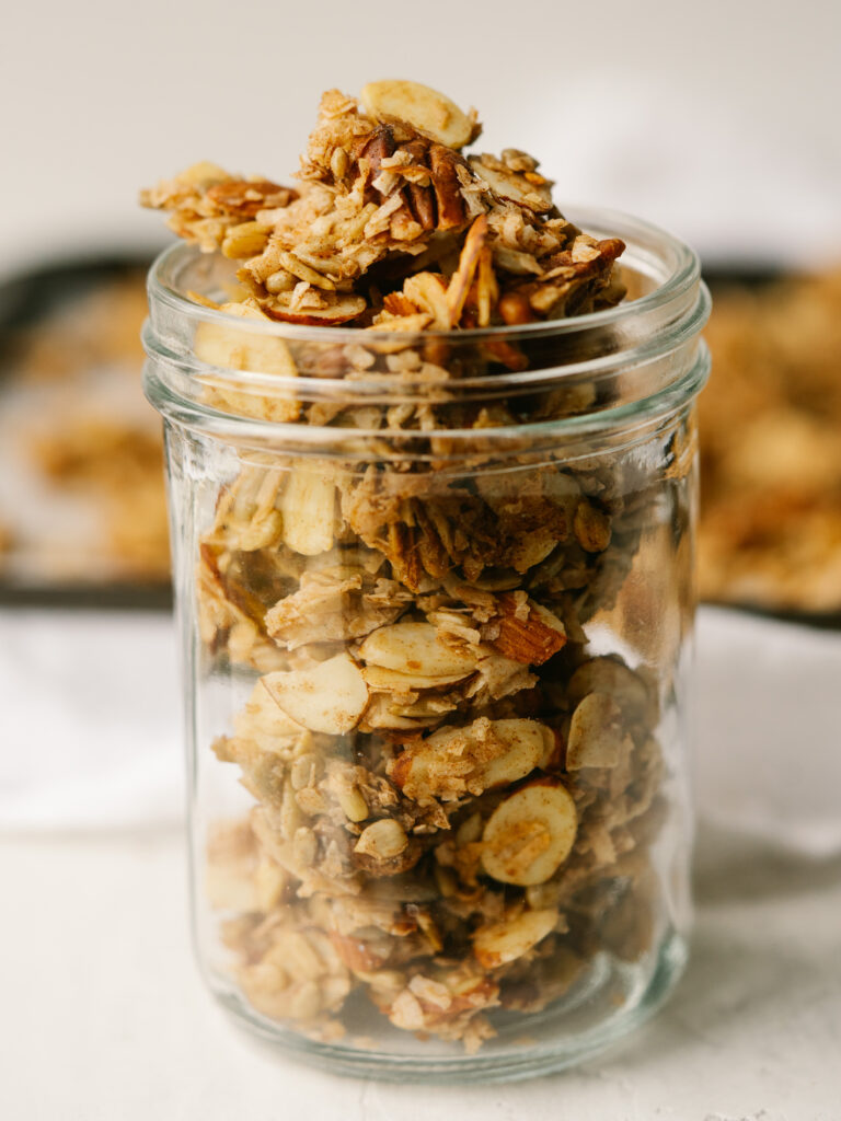 Side view of cinnamon granola in a glass jar