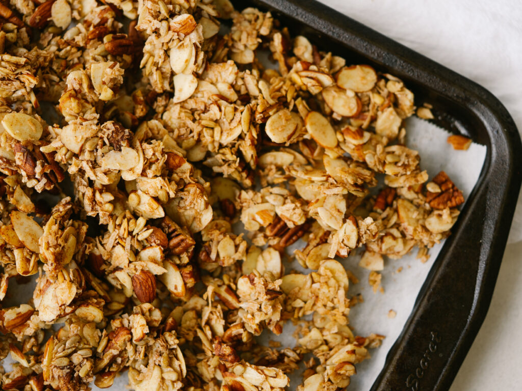 Above view of crunchy maple granola recipe on a baking sheet lined with parchment