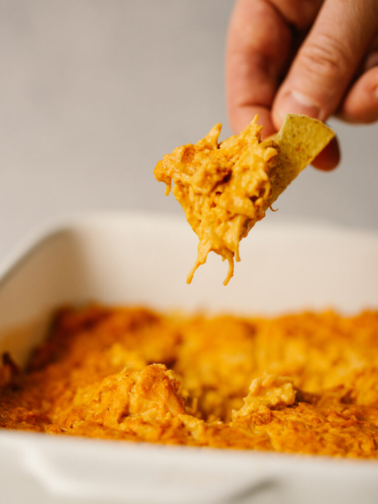 Side view of a chip dipping into pantry buffalo chicken dip