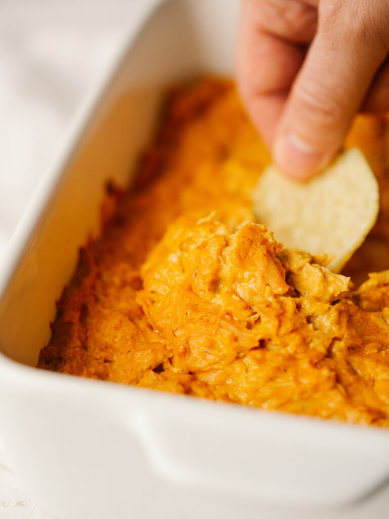 Above view of a tortilla chip dipping into a dairy free buffalo chicken dip