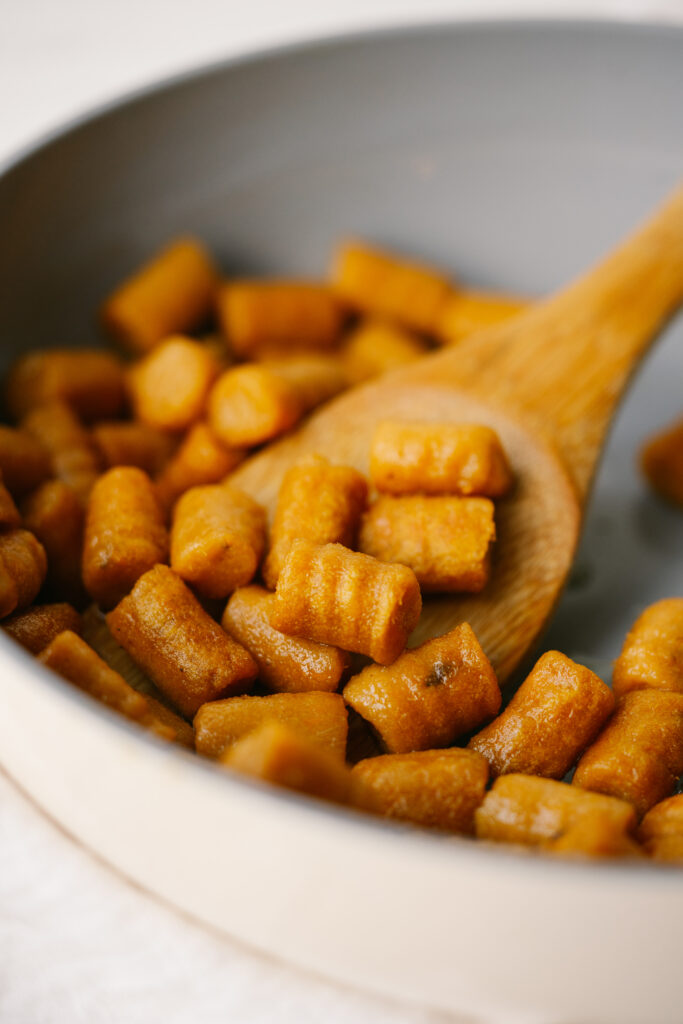 three quarter view of cooked sweet potato gnocchi on a spoon