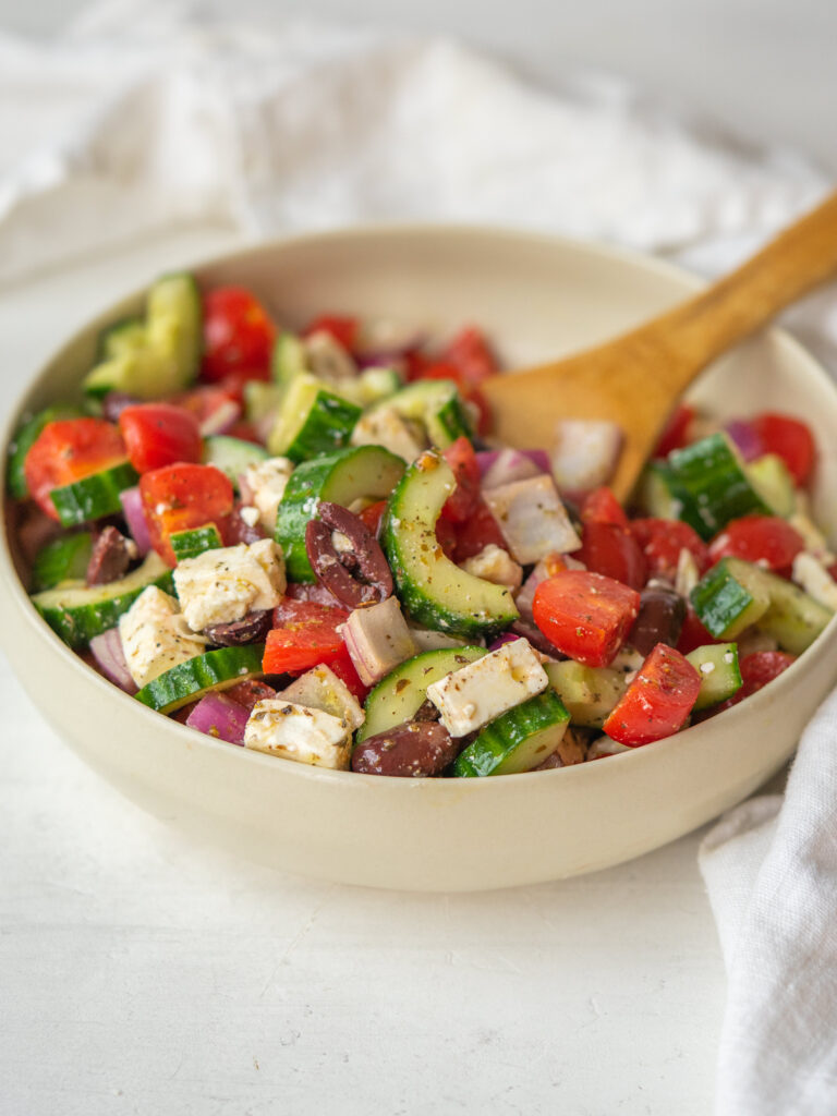 bowl of cucumber greek salad with a spoon in it tossed in a simple greek salad dressing