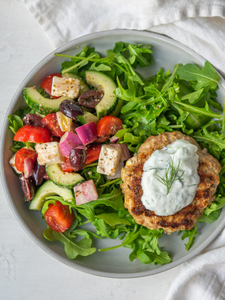 greek turkey burger on a plate with arugula and greek salad