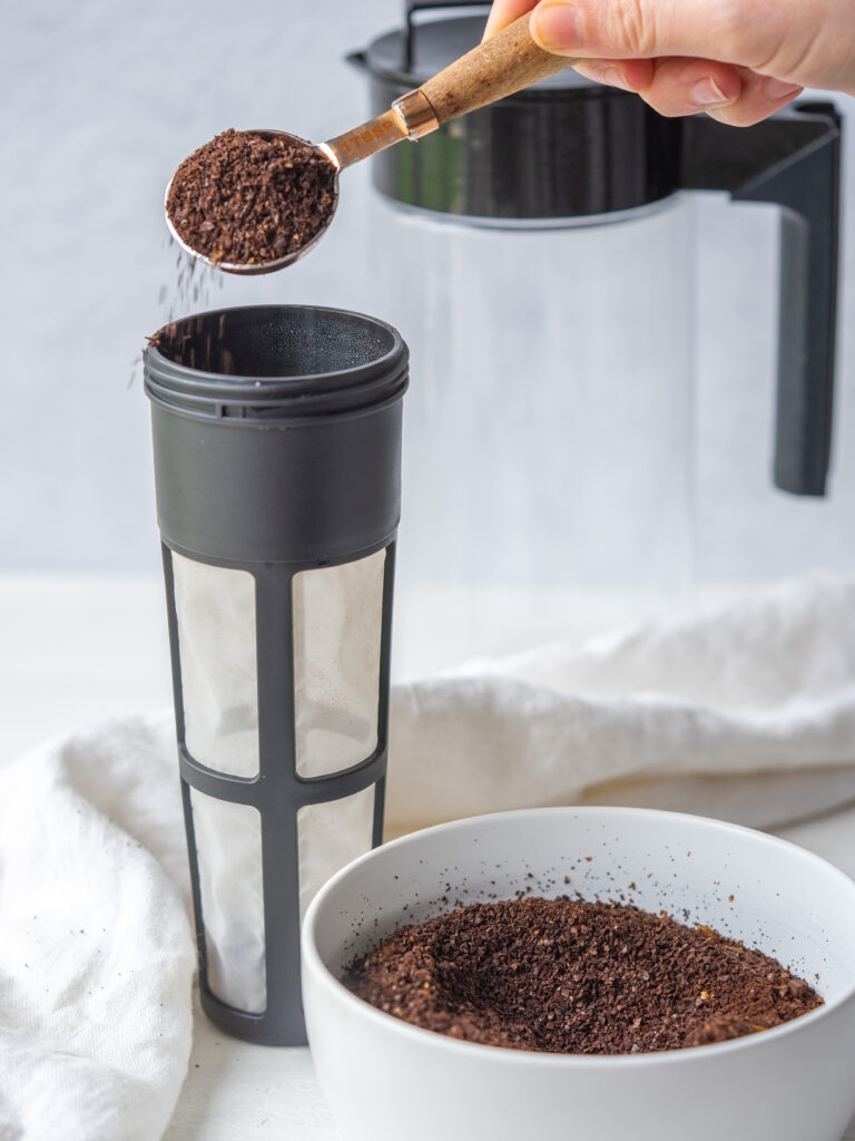 Side view of coarsely ground coffee beans being poured into a cold brew coffee pitcher