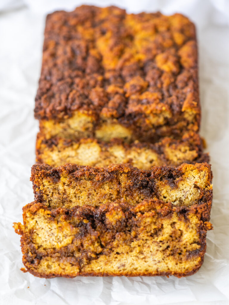 banana bread loaf with 3 slices laying in front