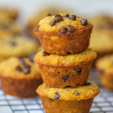 Side view of mini banana muffins stacked on a cooling rack