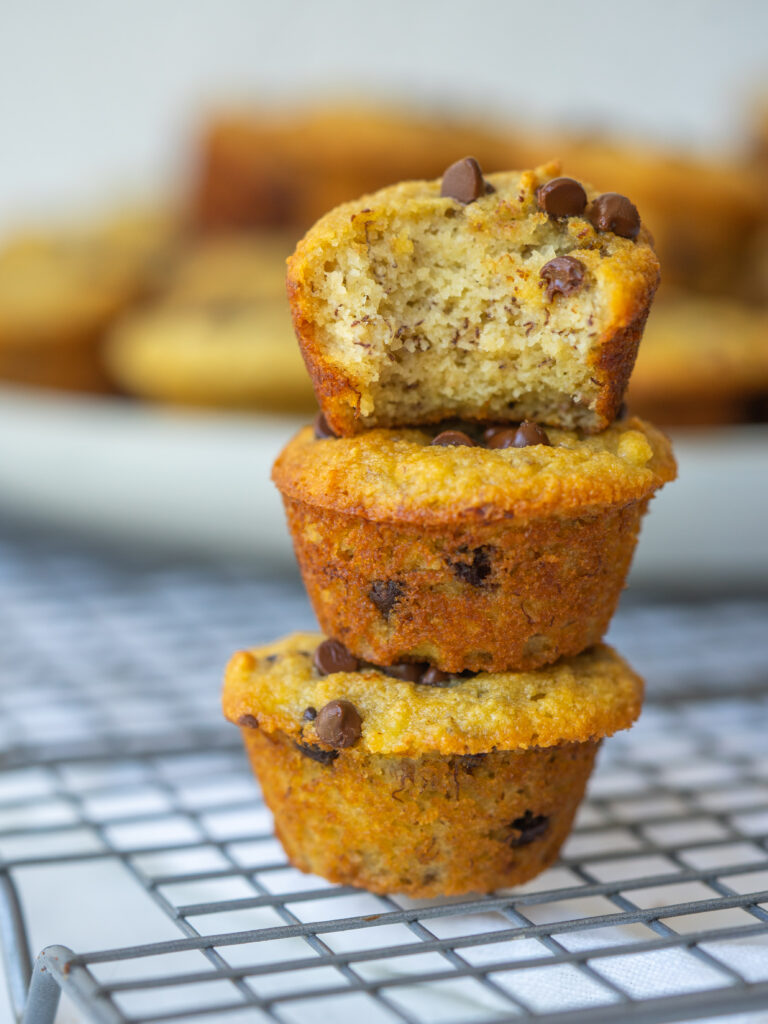 Side view of mini banana muffins stacked up with a bite out of the top muffin