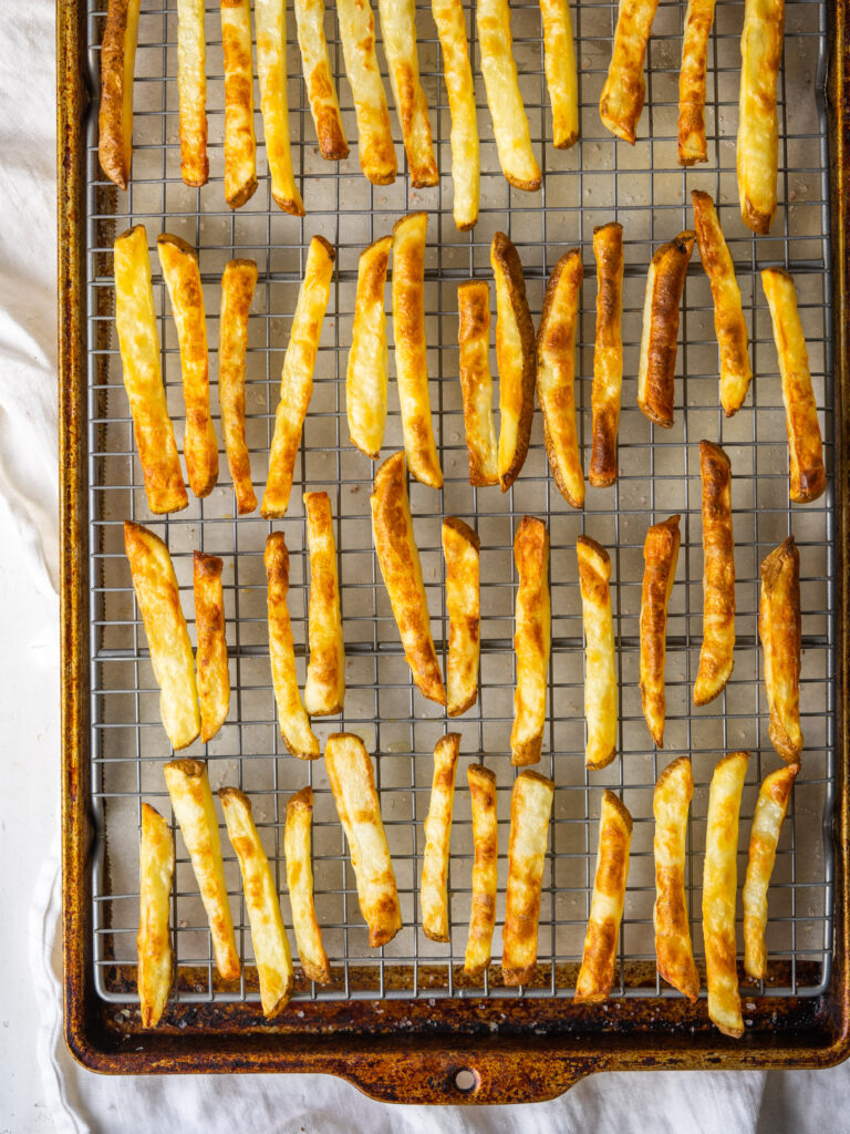 Above view of baked french fries cooling on a cooling rack