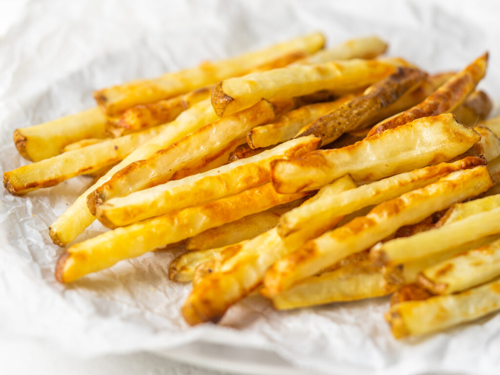 Three quarter view of crispy baked fries on a piece of parchment paper
