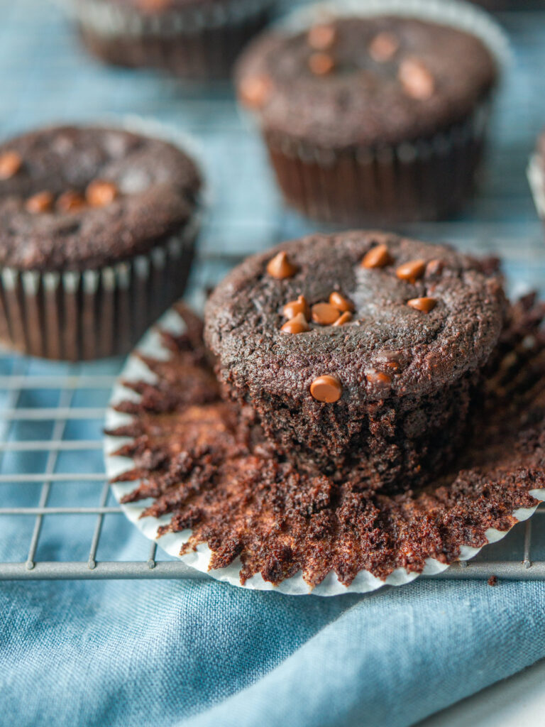 chocolate muffin with the wrapper pulled down sitting on a cooling rack on a blue towel