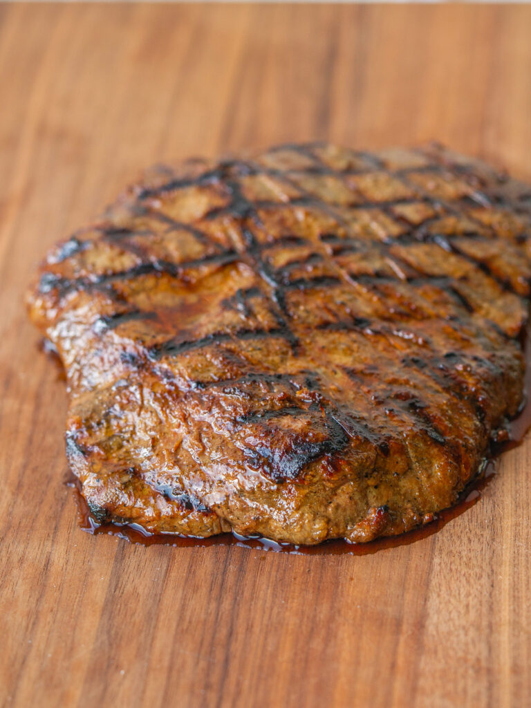 Three quarter view of marinated grilled flank steak on a cutting board