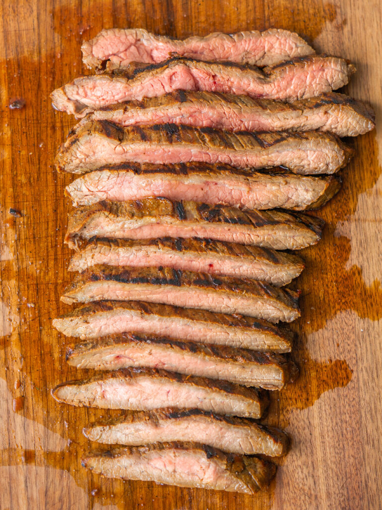 Above view of sliced flank steak on a cutting board