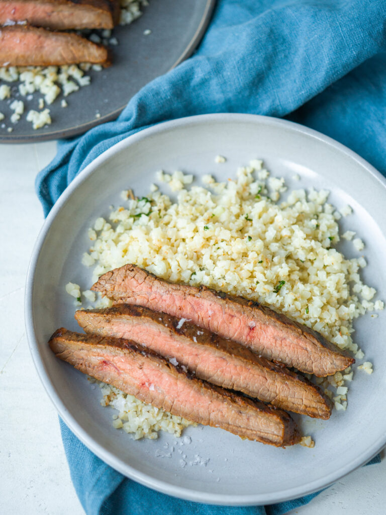 Grilled flank steak slices on a plate with cauliflower rice
